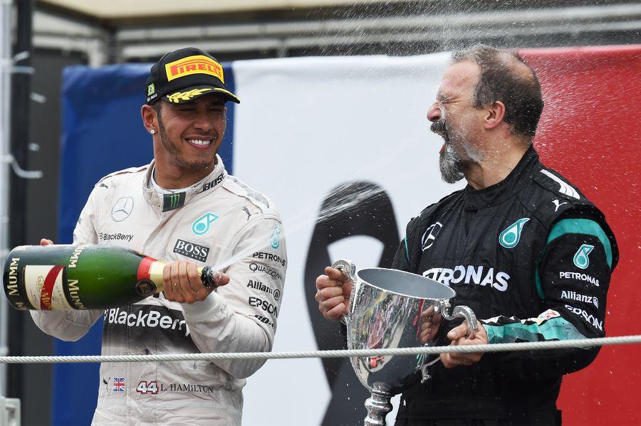 Lewis Hamilton celebrates on the podium with James Waddell