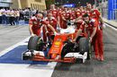 Ferrari mechanics push Sebastian Vettel's car to their garage