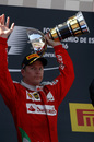 Kimi Raikkonen celebrates with the trophy on the podium