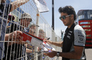 Sergio Perez signs an autograph for fans