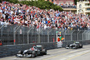 Michael Schumacher waves to the crowd followed by team-mate Nico Rosberg at the finish