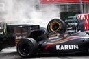 Smoke comes off the crashed cars of Jarno Trulli's Lotus and Karun Chandhok's HRT
