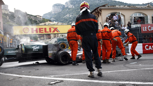 Stewards clear the crashed cars of Jarno Trulli's Lotus and Karun Chandhok's HRT