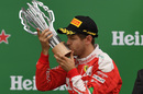 Sebastian Vettel kisses the trophy on the podium