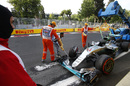 The car of Lewis Hamilton is recovered by the marshals after crashing in Q3