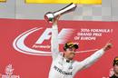 Nico Rosberg celebrates on the podium with the trophy
