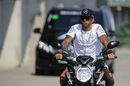 Lewis Hamilton arrives at the track on a motorbike