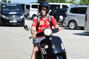 Sebastian Vettel arrives on a scooter