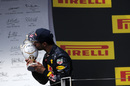 Daniel Ricciardo kisses the trophy on the podium