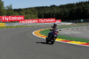 Carlos Sainz rides the track on a scooter