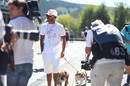 Lewis Hamilton walks through the paddock with his dogs
