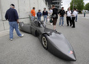 Fans look over a Delta Wing concept car in the pagoda plaza during practice for the Indianapolis 500