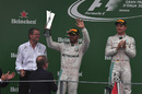 Lewis Hamilton celebrates on the podium with the trophy
