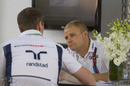 Valtteri Bottas discusses something at the paddock