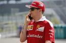 Kimi Raikkonen walks through the paddock