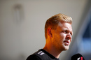 Kevin Magnussen looks on in the paddock