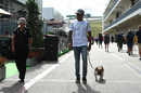 Lewis Hamilton walks through the paddock with his dog