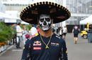 Daniel Ricciardo walks through the paddock with sombrero and face paint