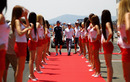 Grid girls form a guard of honour for the arriving drivers