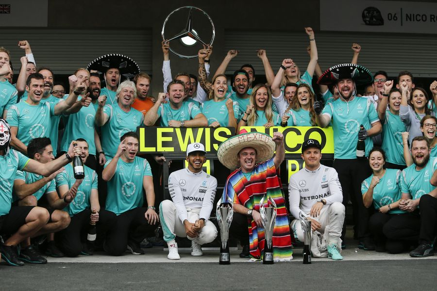 Lewis Hamilton and Nico Rosberg celebrate with the team
