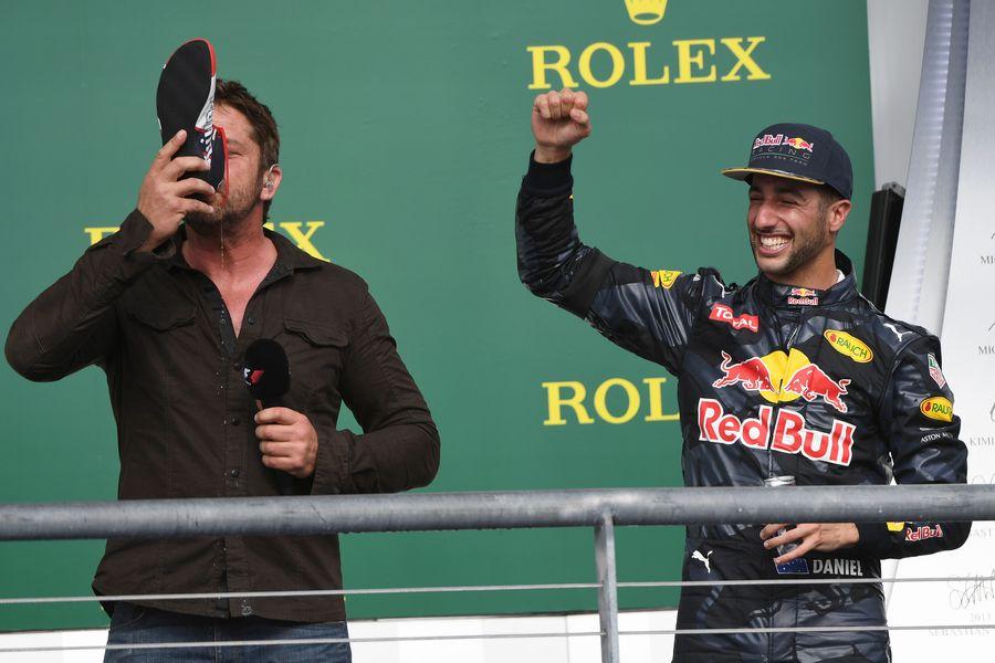 Gerard Butler drinks from the boot of Daniel Ricciardo on the podium