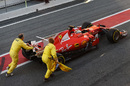 Sebastian Vettel is pushed by the marshals in pit lane