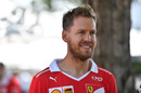 Sebastian Vettel arrives the paddock with a smile on his face