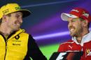 Nico Hulkenberg speaks with Sebastian Vettel during the press conference