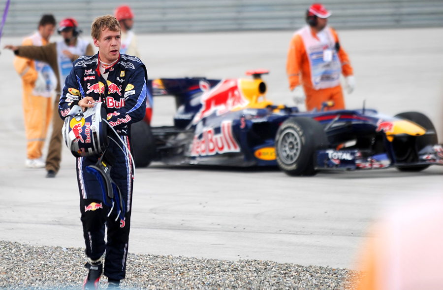 Sebastian Vettel walks away from his car after his collision with Mark Webber