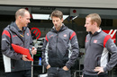 Romain Grosjean talks with engineers at the garage