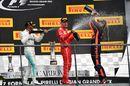 Race winner Lewis Hamilton celebrates on the podium with Sebastian Vettel and Daniel Ricciardo with the champagne