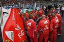 Ferrari mechanics observe the car of Kimi Raikkonen with Turbo issues on the grid
