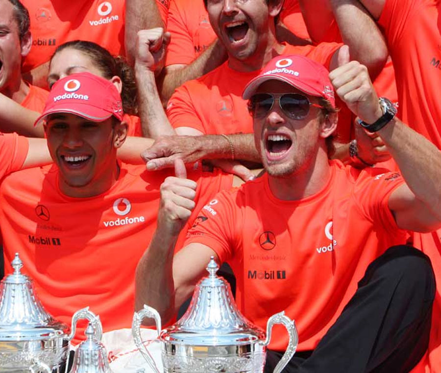 Lewis Hamilton and Jenson Button celebrate with the team