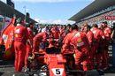 Ferrari mechanics observe the car of Sebastian Vettel on the grid with technical issues