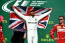 Race winner Lewis Hamilton celebrates on the podium with the Union Jack flag
