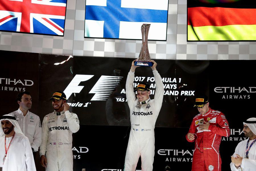 Race winner Valtteri Bottas celebrates on the podium with the trophy alongside Lewis Hamilton and Sebastian Vettel