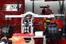 Mechanis work on the rear of Fernando Alonso's Ferrari