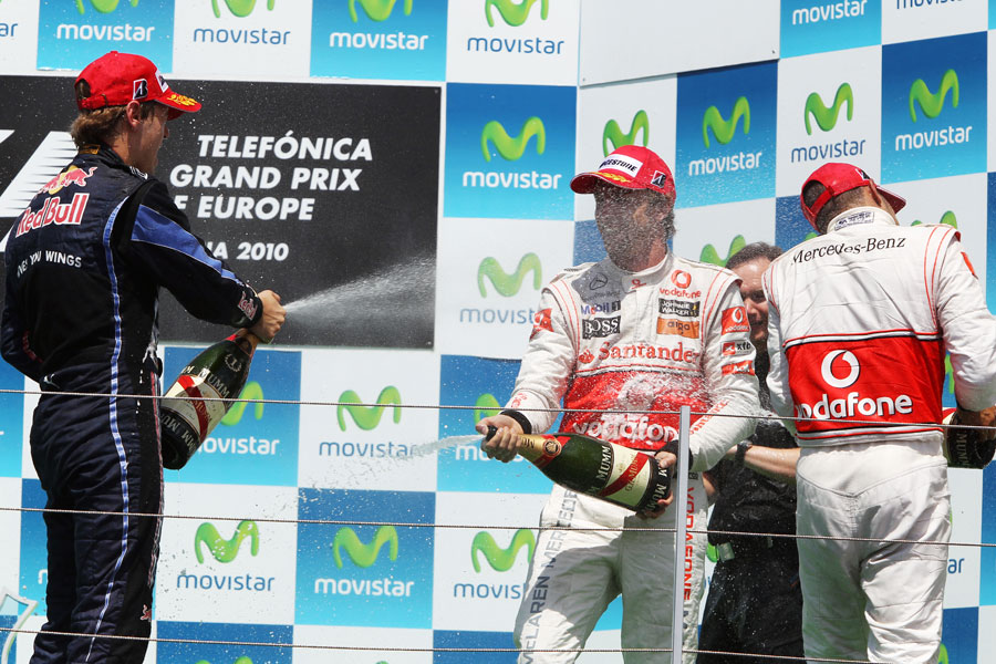 The top three spray champagne on the podium