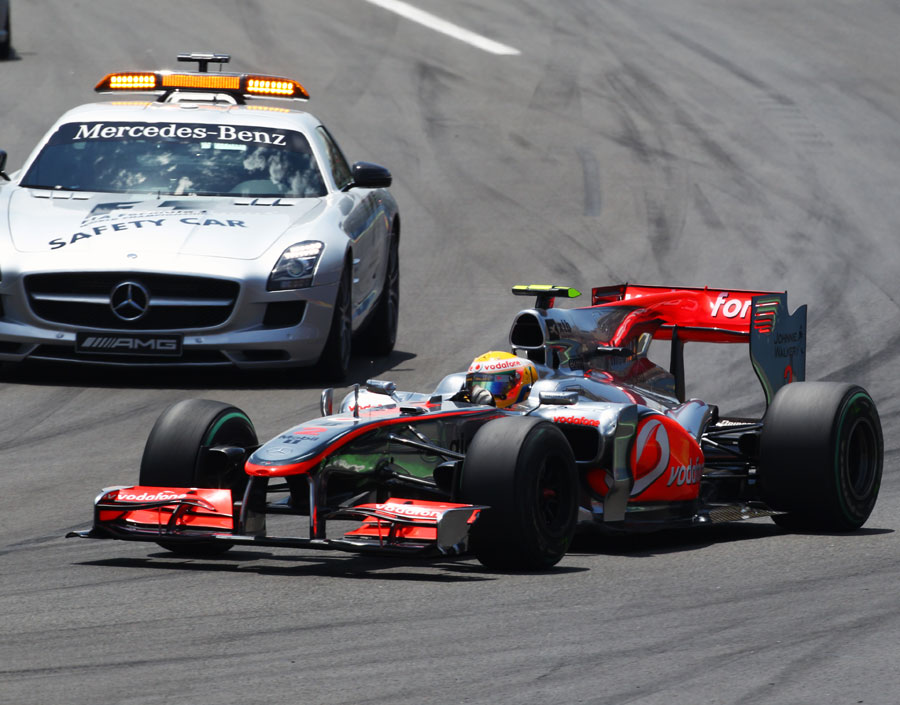 Lewis Hamilton overtakes the safety car as it joins the track