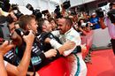 Race winner Lewis Hamilton celebrates in parc ferme with the team