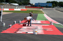 Workers prepare trackside circuit signage