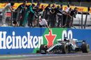 The Mercedes team celebrate on the pit wall as race winner Lewis Hamilton crosses the line