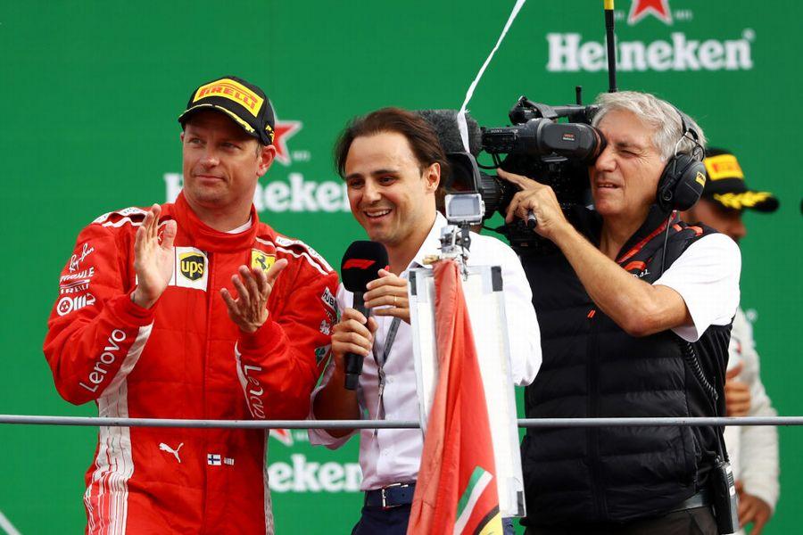 Kimi Raikkonen speaks with Felipe Massa on the podium