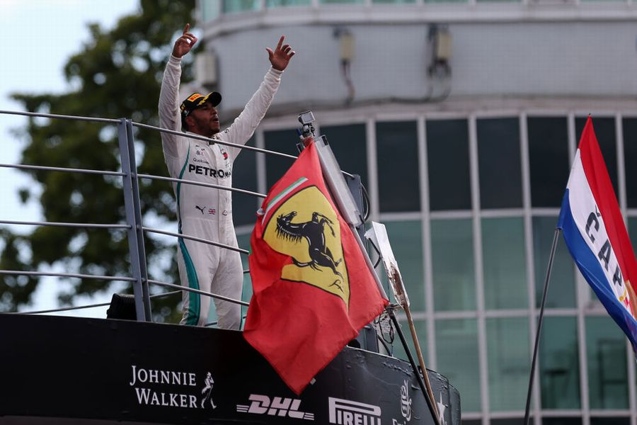 Race winner Lewis Hamilton celebrates on the podium