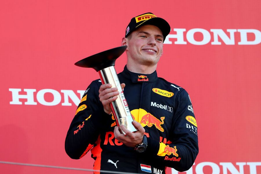 Max Verstappen celebrates on the podium with the trophy