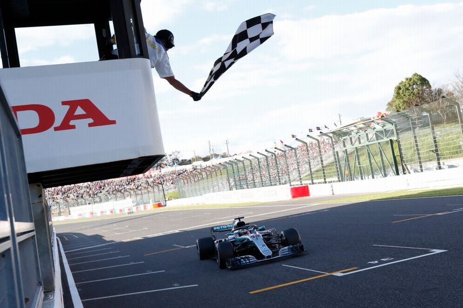 Race winner Lewis Hamilton takes the chequered flag
