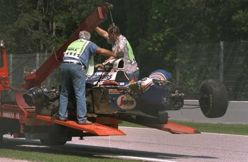 Ayrton Senna's car is loaded on to a truck after he had been rushed to hospital