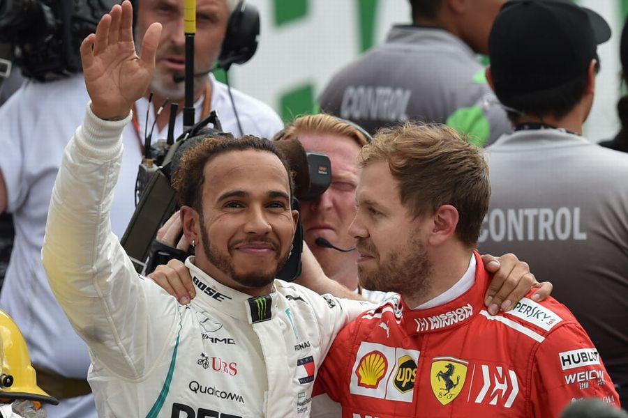 Lewis Hamilton waves at the crowd as he hugs Sebastian Vettel in parc ferme