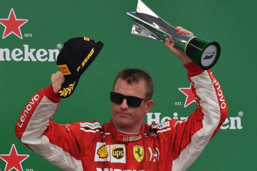 Kimi Raikkonen celebrates on the podium with the trophy