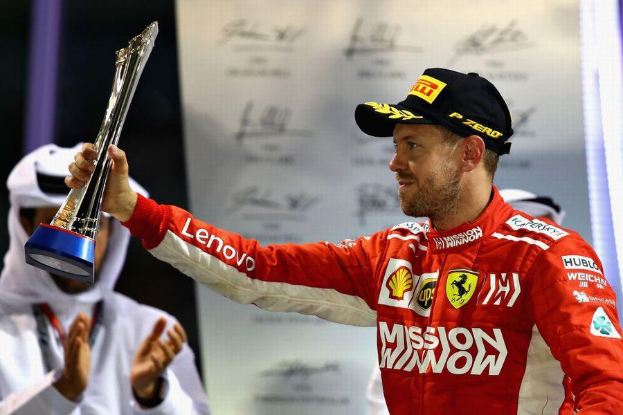 Sebastian Vettel celebrates on the podium with the trophy